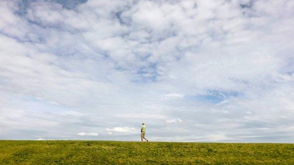 Mann läuft auf Deich vor weitem Himmel